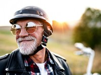 A happy, elderly man sitting on his motorcycle in the country.