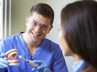 Dentist demonstrating use of electric toothbrush to female client