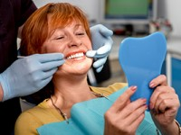 Woman sitting in dentist's chair looking at her teeth and gum health in a mirror.