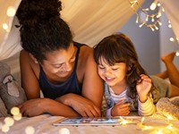 Mother and daughter smiling and using digital tablet.