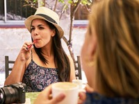 Woman smoking an e-cigarette while enjoying coffee with a friend.