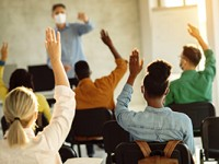 Back view of group of students raising their arms during a class at lecture hall.
