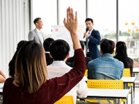 A woman is raising hand up while businessman is speaking in training at the office.