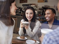Four smiling friends having coffee at coffee shop.