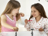 Two girls laughing and brushing their teeth.