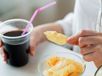 Individual snacking on chips and soda. These are bad foods for your oral health.