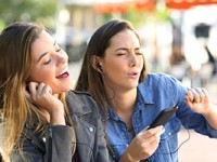 Friends listening to music on smartphone and singing.