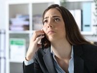 Impatient female executive calling on phone at the office.