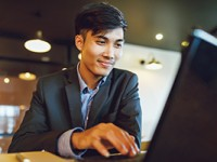 Smiling asian businessman in suit working with laptop