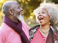 Senior couple laughing while walking outdoors.