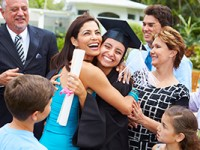 Hispanic student and family celebrating graduation.
