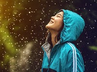 Happy Asian woman letting raindrops fall from the sky and hit her face.