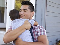 Father Hugging Son Sitting On Steps Outside Home