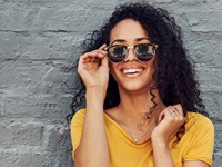 A young woman wearing sunglasses and smiling while standing against a gray wall outdoors.