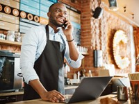 African American male accepts a pre-order on a cell phone while working on a laptop.