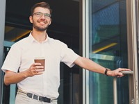 Happy male leaving building while holding a coffee.