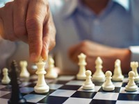 Two businesspeople playing chess board.