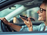 Side view of a smiling business woman using smartphone, recording voice message while driving a car.