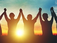 Silhouette of group business team making high hands over head as sun sets.