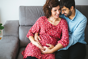 Loving, happy pregnant couple relaxing at home.