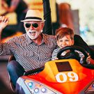 Grandfather and grandson enjoying a ride at an amusement park.