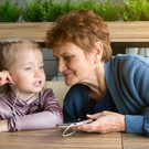 An elderly woman on a smartphone turned on an audio tale for a little girl in headphones.