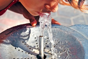Girl drinking from water fountain. Drinking water is great for overall dental care.