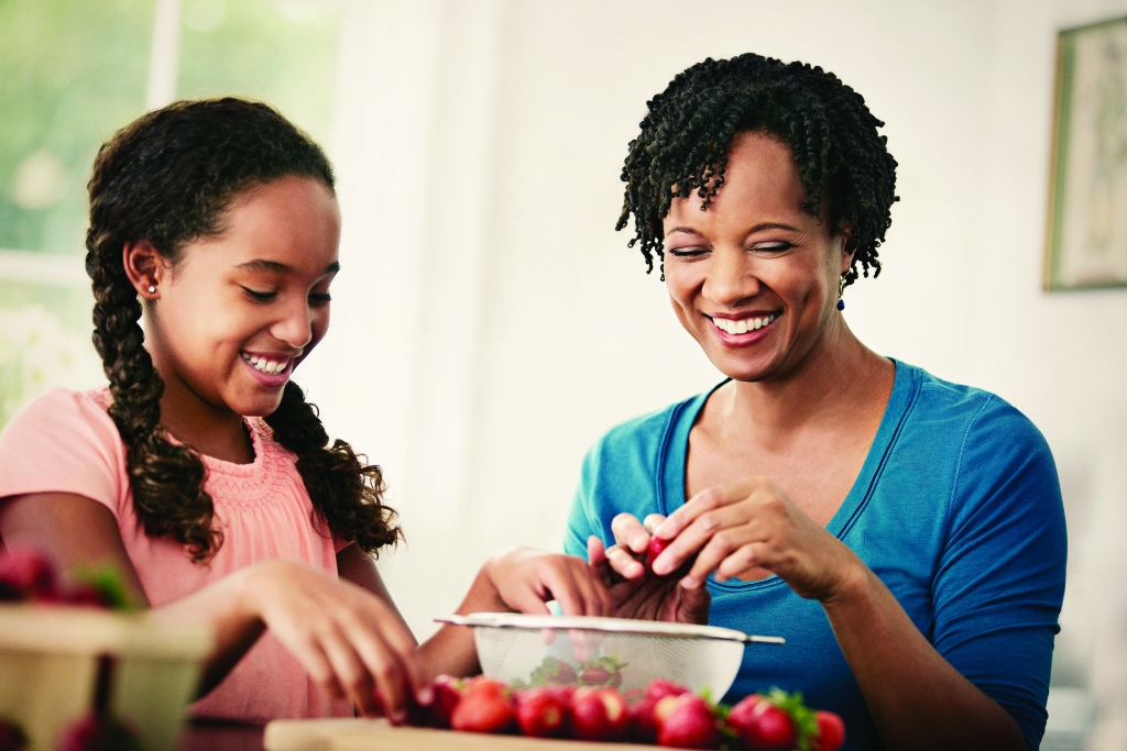 Mother or grandmother preparing strawberries with daughter or granddaughter