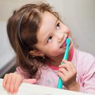 Little girl in pink pajamas brushing her teeth.