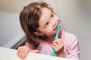 Little girl in pink pajamas brushing her teeth.