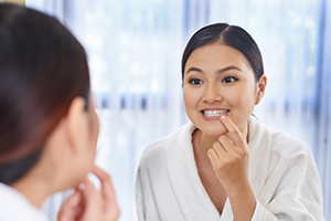Young Asian woman looking at her teeth in the mirror.