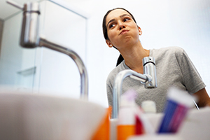 Female in front of a sink rinsing with mouthwash in the morning.
