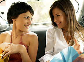 Two women sitting in taxi with shopping bags, smiling at each other