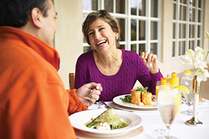 Couple laughing and enjoying dinner.