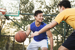 Two young men playing basketball on a public outdoor court