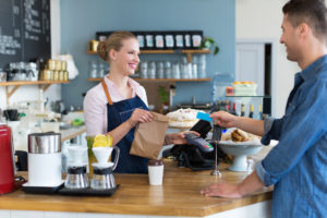 Happy waitress working at small business with employee benefits.