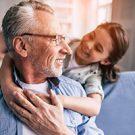 Happy girl hugs her grandfather on the sofa