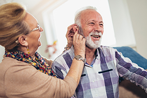 Elderly woman helping elderly man with his hearing aid.