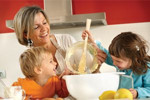 Mom baking with young boy and girl.