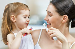 mother and daughter brush teeth
