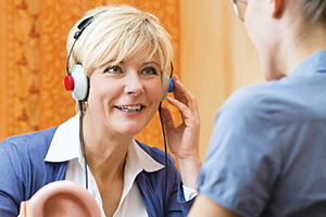 Woman taking a hearing test to check for hearing loss and see if she needs hearing aids.