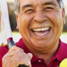 Guy smiling with a tennis ball and racket