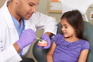 Dentist showing a child how to brush their teeth