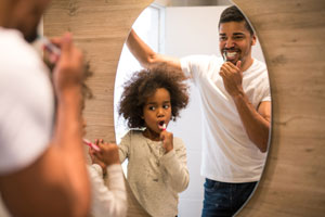 Father and daughter brushing their teeth in a mirror
