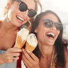 Two women holding ice cream cones and laughing.
