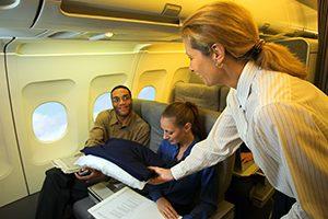 Flight attendant giving passenger pillow and blanket