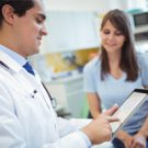 Doctor using digital tablet while consulting patient at hospital