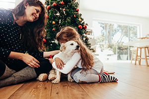 Happy mother and daughter celebrating Christmas with their dog.