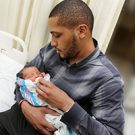 African American Father Holding and Feeding Newborn Infant Baby