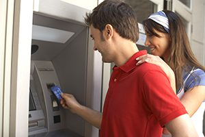 Couple using ATM